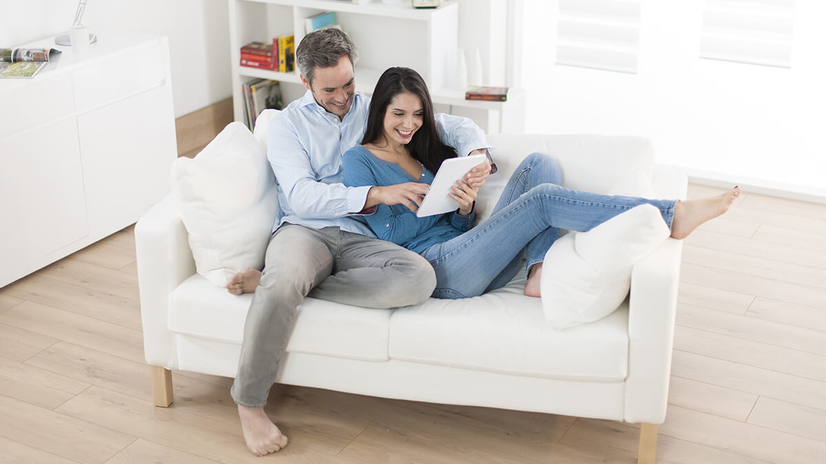 un homme et une femme sur leur canapé lisant