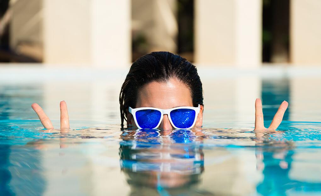 femme dans une piscine faisant le signe de la victoire
